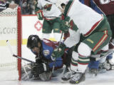COWP102 - Colorado Avalanche's Scott Hannan, left, lays on the legs of Avalanche goalie Peter...