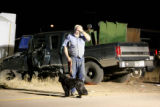 Terence Rice, cq of Erie, Colo; with his dog Daisy, stand in front of the accident scene where two...