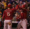 Jeff Salazar congratulates Mark Reynolds after Reynolds' solo home run in the fourth inning of...