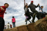 MJM011 Flying through the air from one hay bale to the next, Homero Munoz (cq), right, carries his...