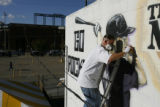 DM0120     Artist Adam Moorhead puts the finishing touches on a 20-foot mural of Colorado Rockies'...