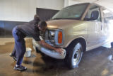 Akim Malik (cq) washes a 14 passenger Chevy Savana van at the American Coach company Monday...