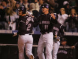 Brad Hawpe and Troy Tulowitzki look back on the field as they score on a double to shallow left by...