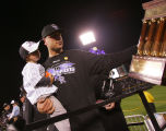 Matt Holliday holds his son Jackson while taking the National League Championship trophy after the...