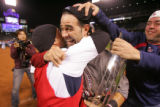 [8334]  Boston Red Sox Mike Lowell gets a congratulatory hug from his brother, Victor Lowell,...
