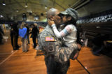 Staff Sergeant Jamie Roberts shares a long awaited laugh, hug and kiss from his daughters Trynity,...