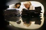 (from left) Staci Fong (cq) and Jennifer Pohl (cq) arrange a stack of clothes at the Men's...