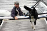 "Steve Paul (cq) waits in his ski boat on Grand Lake as ""pepper"",  a neighbor's dog stops..."