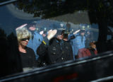 Lieutenant Colonel M. Anthony Padilla (cq) (seen through window) salutes as the body of State...