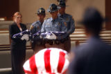 Colorado State Troopers carry three American Flags who will  be handed over to the family of...