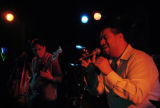 Martin Soto (cq, right), vocalist for Jazz del Barrio sings as Vince Vigil (cq, left), and other...