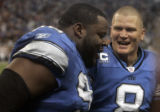 [EPS101] Detroit Lions defense men Shaun Rogers, left, is cheered on by Detroit Lions quarterback...