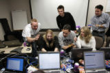 Employees for the IQ Navigator in the Denver Tech Center gather around Dawn Rew, second from left,...