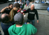 Boston red Soxx player Mike Lowell is surrounded by autograph seekers at Fenway Park in Boston,...