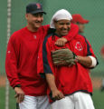 Boston Red Sox manager Terry Francona hugs Manny Ramirez during team practice Tuesday Oct. 23,...