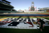 Coors Field grounds keeper Tim Holt (cq) puts the finishing touches on the World Series Logo on...