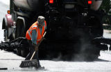 Eddie Gonzalez (cq) sweeps chips  during a Chip Seal operation on 18th Avenue  and Depew street in...