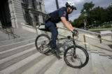 0136 State patrol technician Gabriel Velasquez, CQ, rides his bike down the South steps of the...