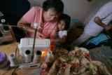 Alicia Garcia, (cq) works at her home on sewing projects with granddaughter Isabella Pena, 4...