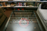 An original wood pattern mold rests under a glass top table with reflection of books on the shelf....