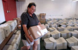 (AURORA, Colo., Sept 2, 2004) Michelle Aree Smith, volunteers unpacking school supplies at the...