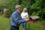 Dennis Nelson and Denise Nelson puts bird feed to the bird houses in the backyard of their...
