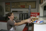 Sheryl prepares to take an order to a table. Sheryl and Lester Thorne working at the Loaf and...