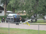 Police investigators look at the scene of an accident following a police chase that ended with a...