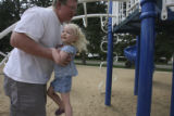 Tim Ellis hauls his daughter, Kiley, 2, to the slide at a local park before Kiley has a nap and...