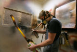 At the Colfax Guitar Shop, employee Kyle Jones spray paints the neck of this electric guitar on...