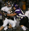 (JPM327) - Arapahoe Warriors Bill Mercer, left, is stopped by No. 3-ranked Douglas County Huskies...