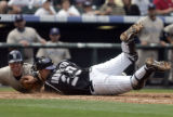 Rockies catcher Chris Iannetta dives into a sliding San Diego Padres' Morgan Ensberg, left, in the...
