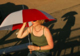 Shannon Barnes (cq), of Pueblo, keeps the sun at bay with her umbrella as she watches mutton...