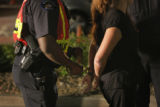 Aurora police officer Everett Williams, left, handcuffs a woman who failed a sobriety test after...