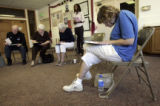 Aurora resident Barbara Hoover (cq), 55, right, fills out a health care concern questionaire...