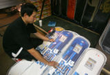 Arnold Kim (cq), 28, of Denver, puts away snowboards in preparation for the Ski Rex sale at...