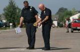 Two Greeley Police officers (lt-rt) Wes Doney, cq, and Ken Gillette, cq  continue to investigate a...