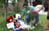 Uncle Jesus Escobar, cq, and great aunt Lourdes Escobar, cq, place a balloon and flowers Tuesday...