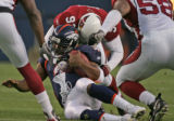 Denver Bronco's back-up quarterback is brought down by Cardinal defender Bertrand Berry, top, in...