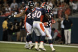 Denver Bronco's teammtes Mark Fenton, left, and Mike Bell, center, hug running back Andre Hall...