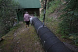 Charlotte Trego (cq) walks along the penstock pipe system, that leads to the hydro-electric plant,...