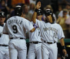 DXF108 - Colorado Rockies' Vinny Castilla, front, is congratulated by teammates, from back left,...