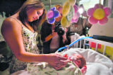 Young mother LaShay Taylor,16, of Baker, MT.,  left, hold her child, Chezni's finger as Local...