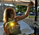 Dorothy Martinez (cq) puts up some Sun Catchers at her booth on Colfax Ave. Friday morning August...