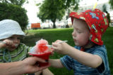 Elliot Moore, 2, left, and his brother Henry Moore, 3, share a snow-cone held by their nanny,...