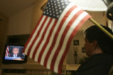 DLM1809  A flag hangs from a lamp in his living room as Mike Mobley listens to President Bush's...