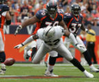 [JOE0509] Denver Broncos Montrae Holland, #70, watches Oakland Raiders Kirk Morrison lose the ball...