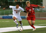 Rangeview Raiders forward #6 ,David Armstrong, and Heritage midfielder Kyle Van Camp fight for...