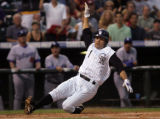 [ES108] -Jamie Carroll slides into home plate for the first score of the Colorado Rockies second...