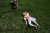 Anton Kiwimagi,  (from mom and teacher) enjoys the tactile feel of the grass outside as Jenna...